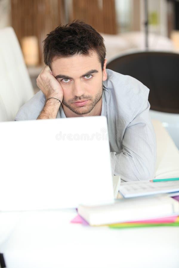Homem furado que usa o portátil imagem de stock