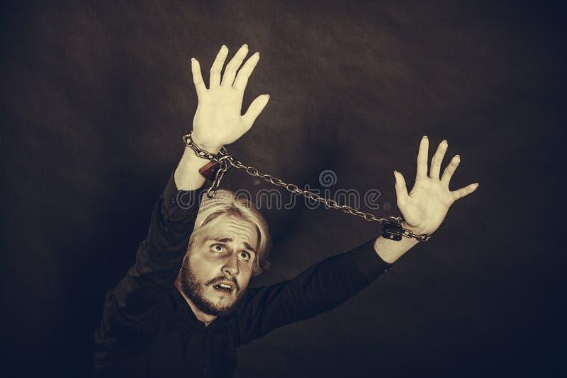 Homem furioso com mãos acorrentadas, nenhuma liberdade fotografia de stock