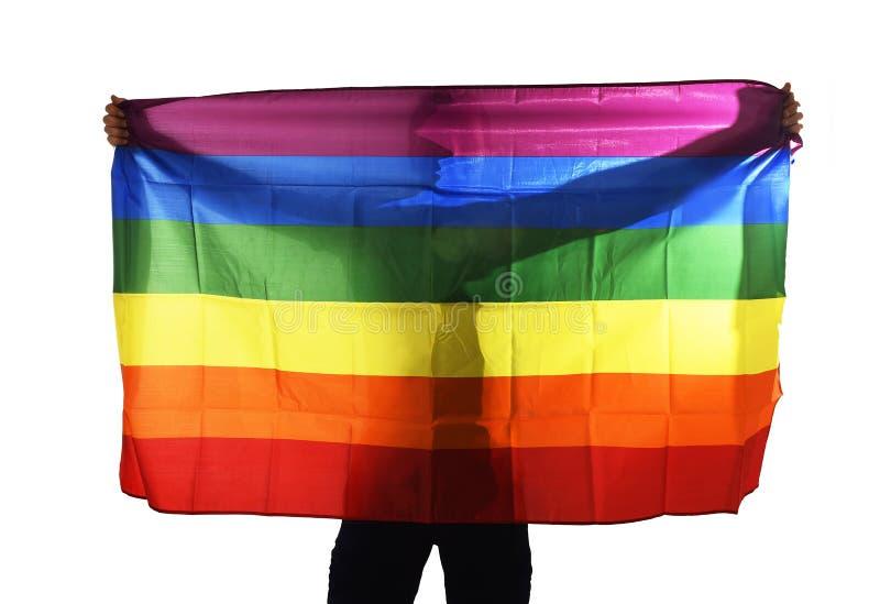 Homem gay orgulhoso novo que espalha a bandeira homossexual do orgulho grande largo com sua sombra atrás do pano imagem de stock