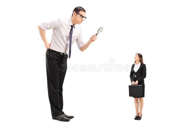 Homem gigante que olha a mulher através da lente de aumento imagens de stock