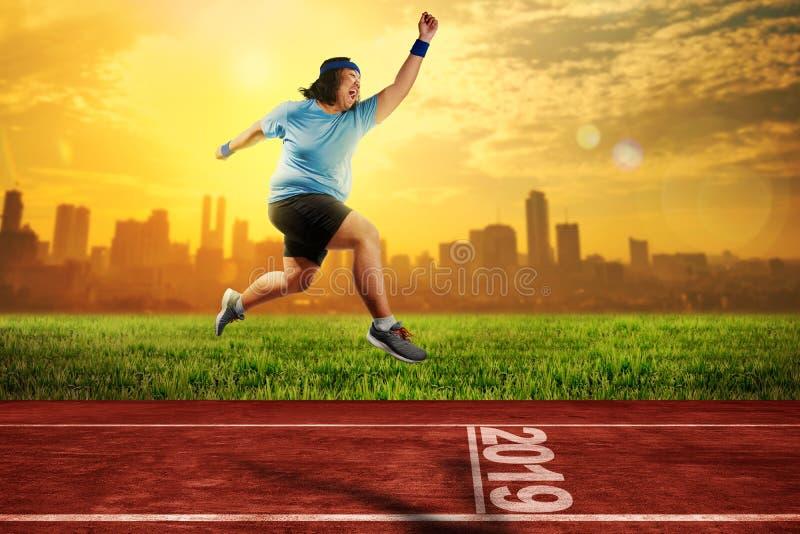 Homem gordo asiático atrativo que corre na pista de atletismo com o 2019 insensibilizado foto de stock royalty free