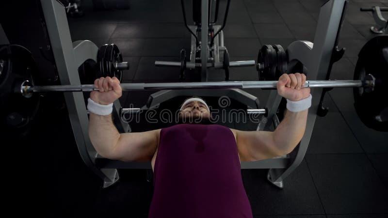 Homem gordo motivado que levanta mal o barbell, exercícios de exaustão, estilo de vida saudável fotos de stock royalty free