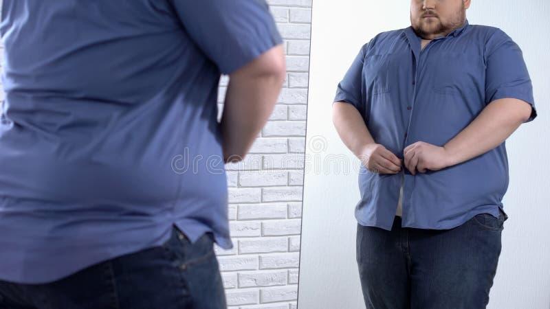Homem gordo que abotoa-se acima da camisa apertada, problema de tamanho grande da roupa, aparência fotos de stock