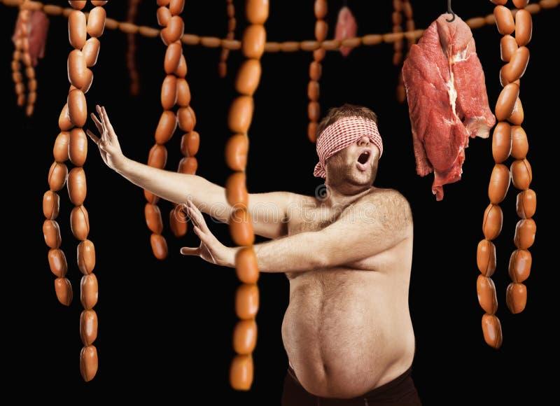 Homem gordo que procura salsichas foto de stock