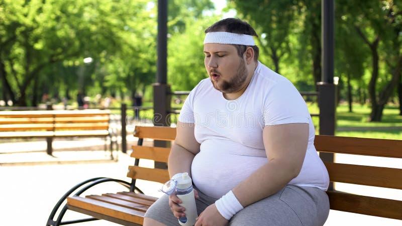 Homem gordo que respiram pesadamente e ácidos aminados bebendo após exercícios intensos imagem de stock