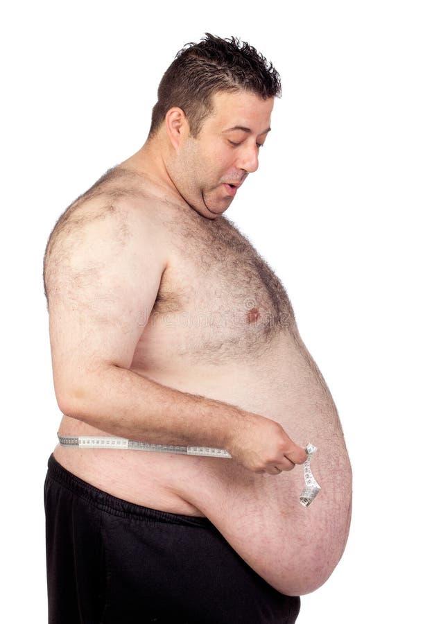 Homem gordo surpreendido com uma medida de fita fotografia de stock royalty free