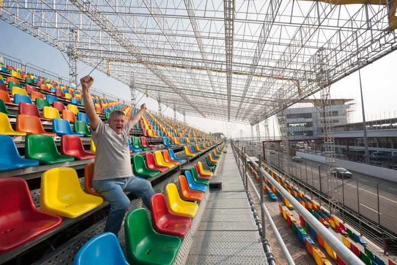 Homem gritando com mãos acima nos assentos para espectadores foto de stock