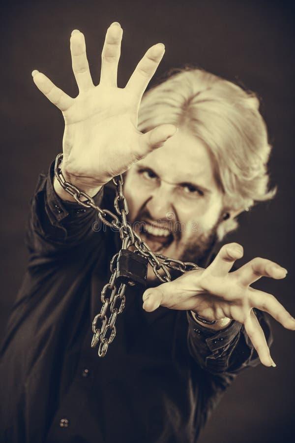 Homem gritando com mãos acorrentadas, nenhuma liberdade fotografia de stock royalty free