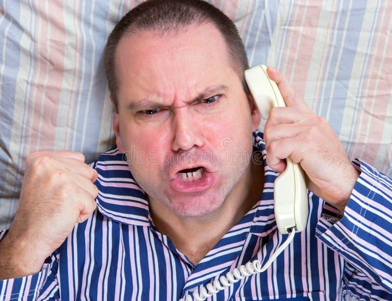 Homem gritando com o telefone na cama foto de stock
