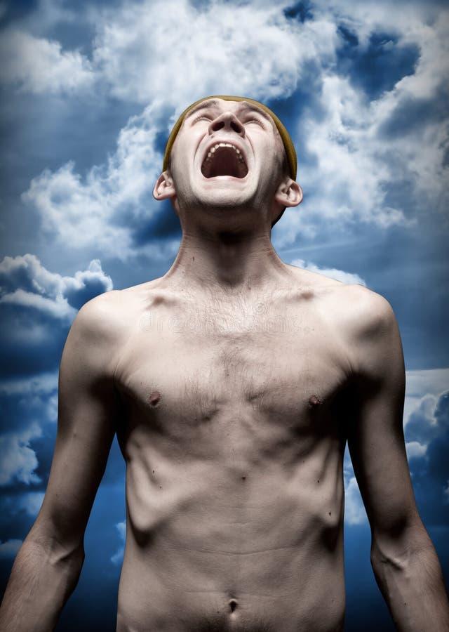 Homem gritando desesperado de encontro ao céu dramático fotografia de stock