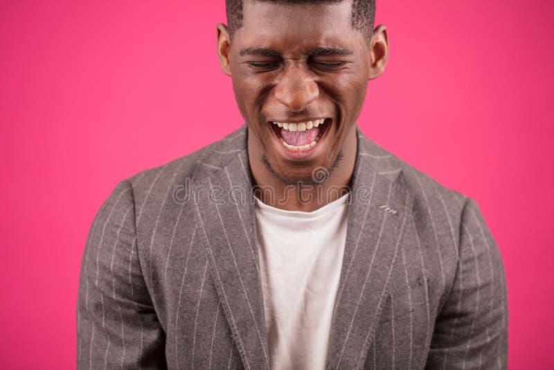 Homem gritando do Afro no fundo do pinck imagem de stock