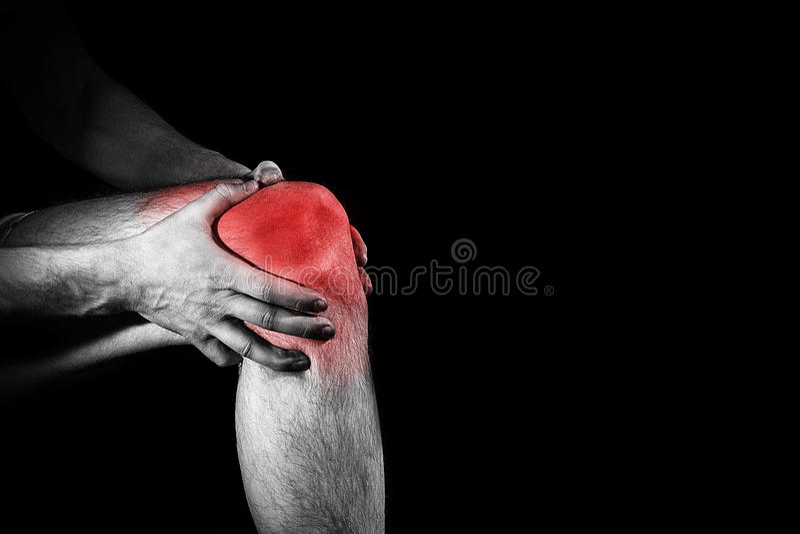 Homem, guardando seu joelho doloroso, pé, experimentando a dor, sp vermelho fotografia de stock