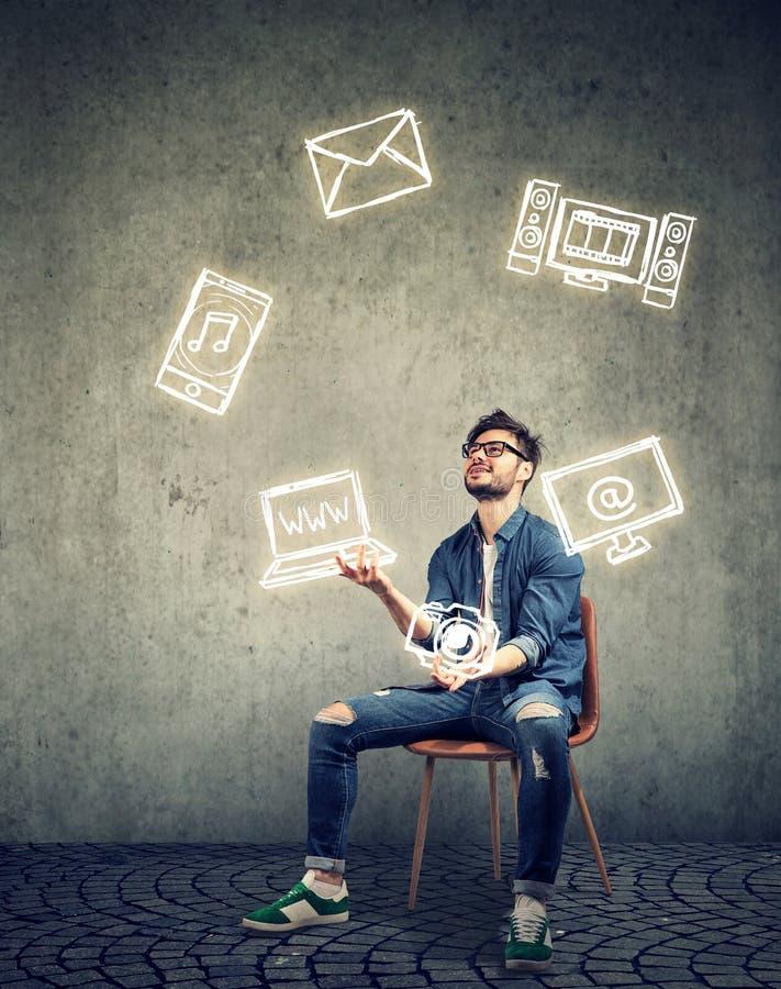 Homem hábil engraçado que senta-se na cadeira e que manipula com ícones dos dispositivos eletrónicos foto de stock