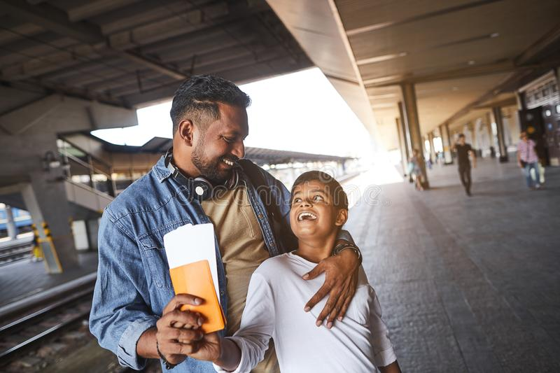 Homem hindu alegre que está com seu filho na estação de trem fotografia de stock