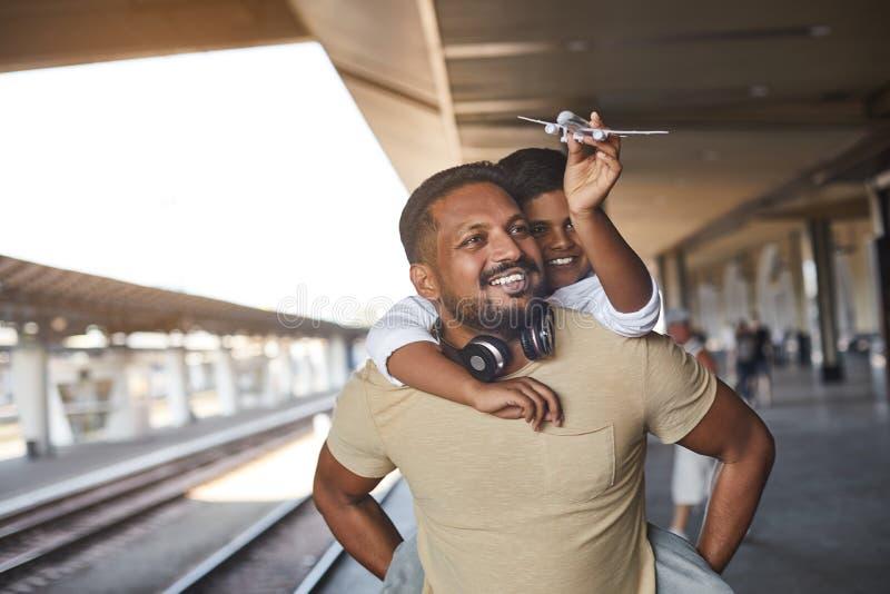 Homem hindu positivo que guarda seu filho na parte traseira imagem de stock