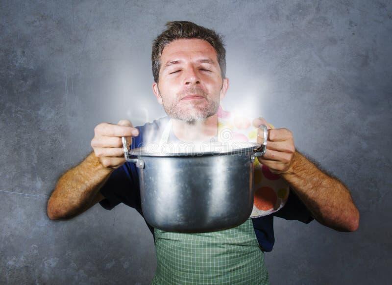 Homem home feliz e orgulhoso atrativo novo do cozinheiro que cozinha a sopa que guarda o potenciômetro da cozinha que cheira gest fotografia de stock
