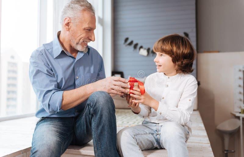 Homem idoso alegre que dá um presente a seu neto fotografia de stock