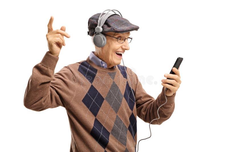 Homem idoso alegre que escuta a música em um telefone imagem de stock royalty free