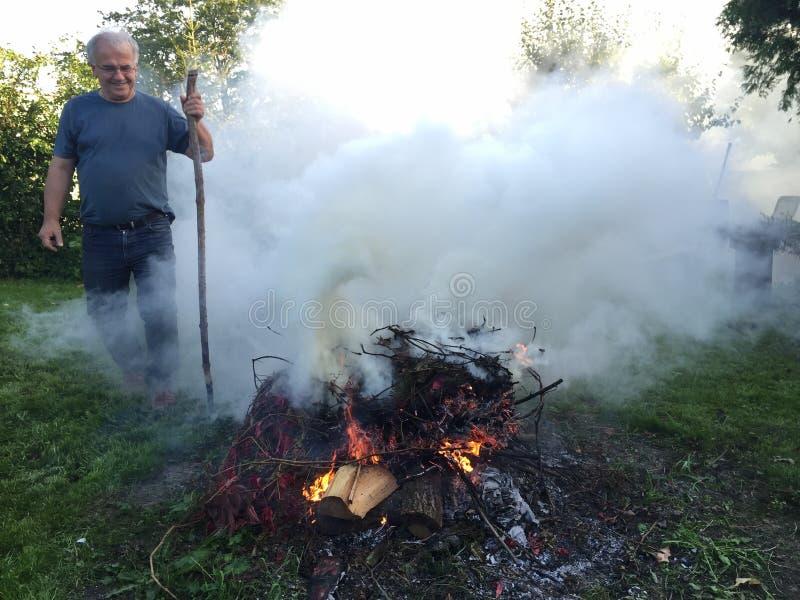 Homem idoso com fogueira do outono foto de stock