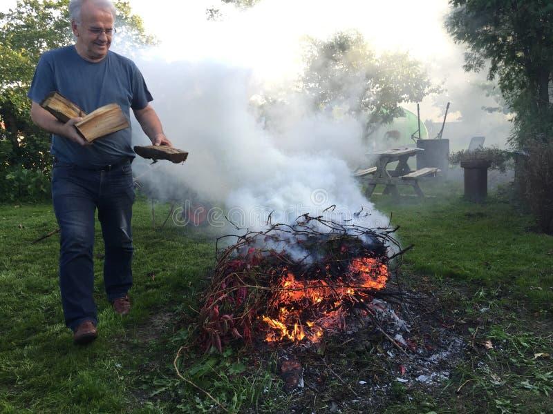Homem idoso com fogueira do outono imagem de stock