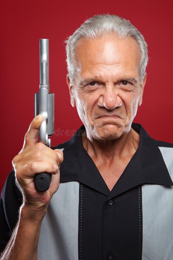 Homem idoso com um revólver fotografia de stock royalty free