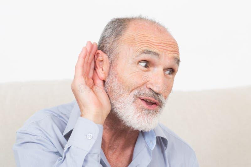 Homem idoso com um surdo-auxílio foto de stock royalty free