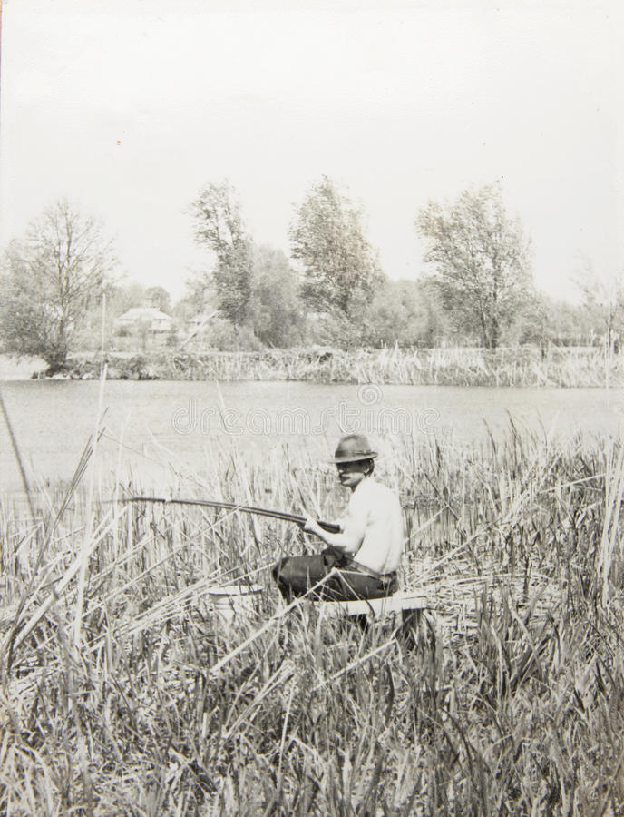 Homem idoso da foto do vintage com uma vara de pesca foto de stock