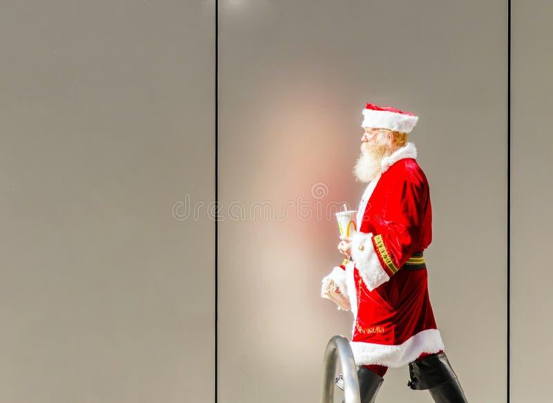 Homem idoso disfarçado como Santa Claus que toma uma ruptura fotografia de stock