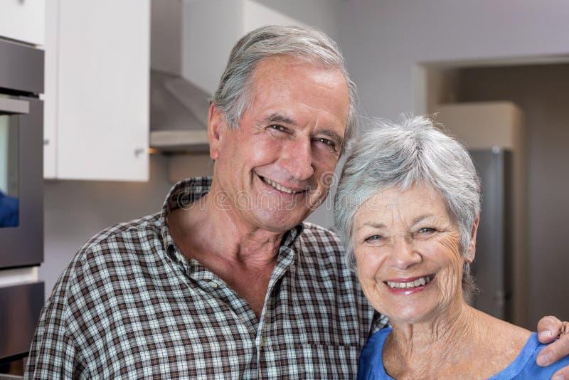 Homem idoso e mulher que estão na cozinha fotografia de stock