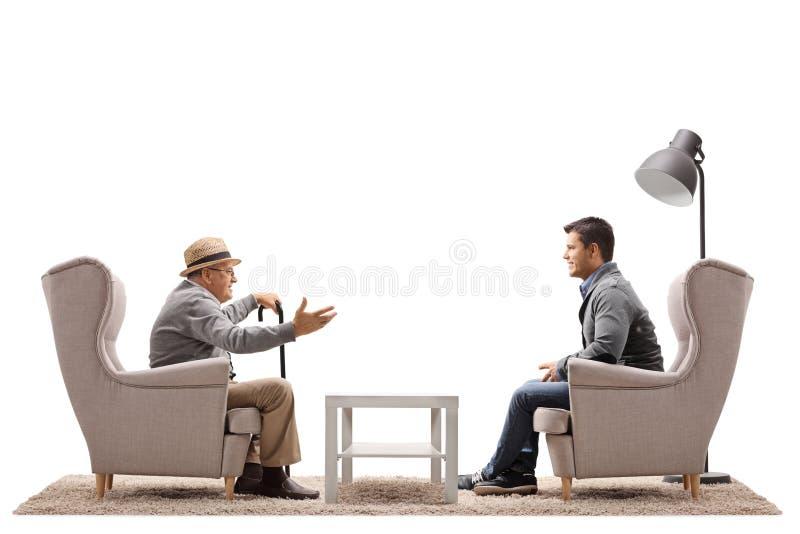 Homem idoso e um indivíduo novo que senta-se nas poltronas e que tem um co fotos de stock royalty free