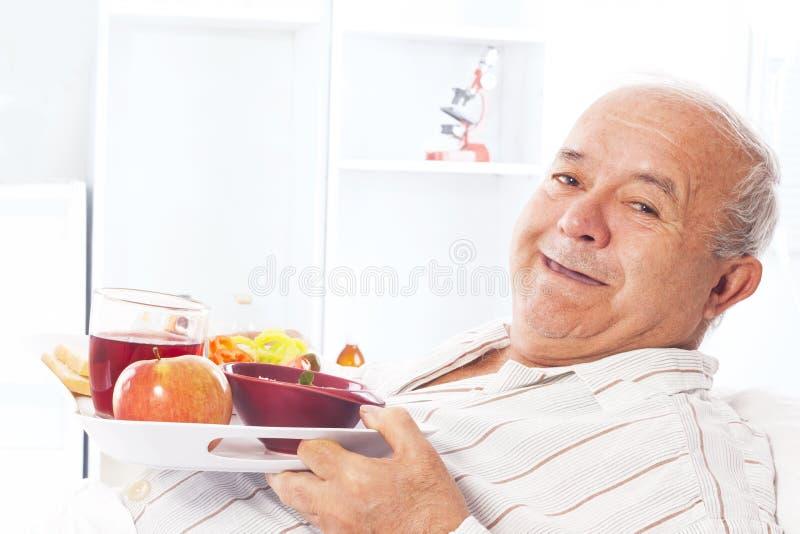 Homem idoso em comer da cama de hospital foto de stock