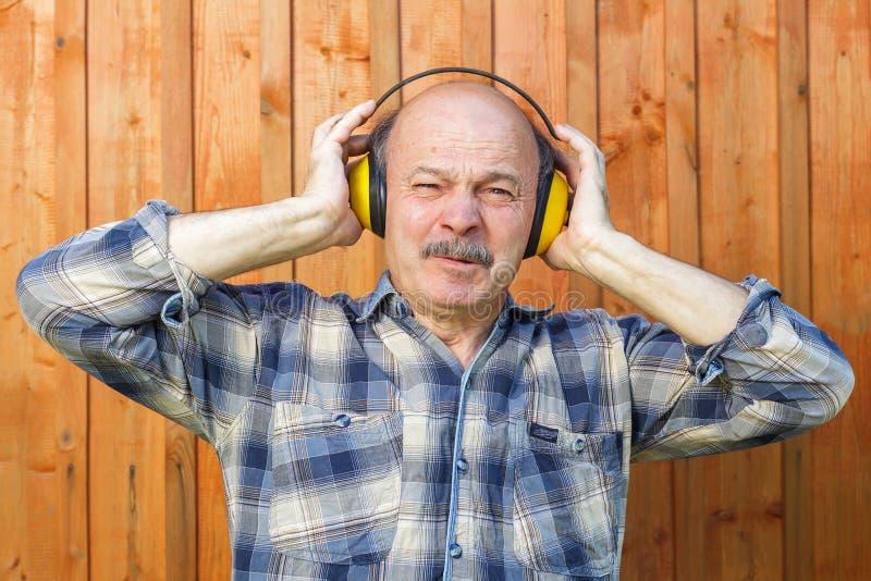 Homem idoso em fones de ouvido protetores de uma construção Soun desagradável imagem de stock royalty free