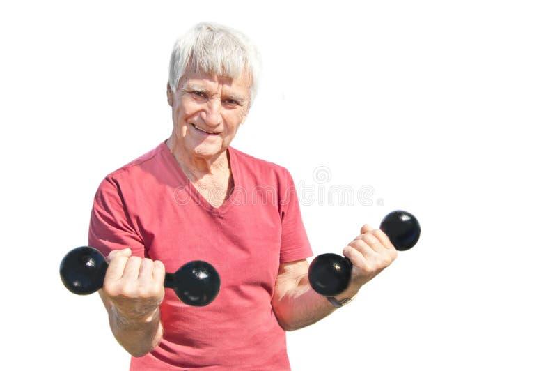 Homem idoso feliz com os pesos pretos isolados no fundo branco Uso de maio ele para a vida saudável imagens de stock