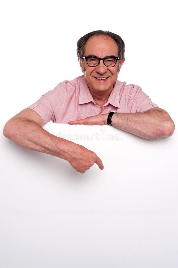 Homem idoso feliz que aponta no quadro de avisos em branco fotos de stock royalty free
