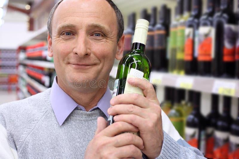 Homem idoso na loja com frasco de vinho imagens de stock