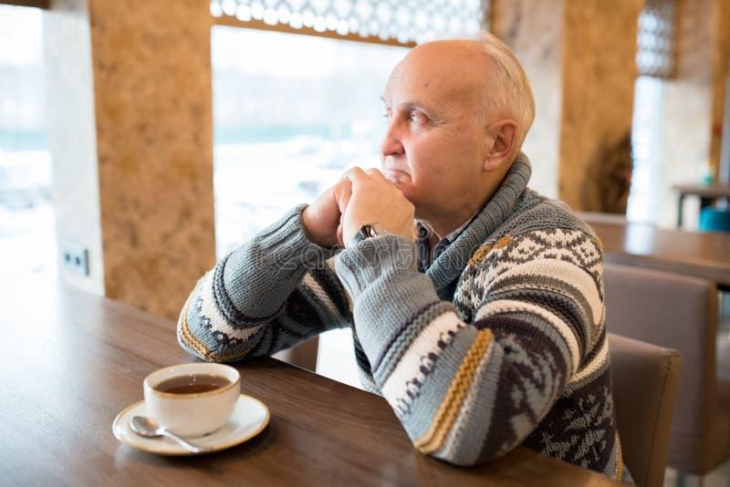 Homem idoso pensativo no café moderno fotografia de stock