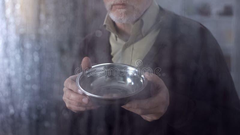 Homem idoso pobre que mostra a bacia vazia, baixa permissão social, falta de dinheiro imagens de stock