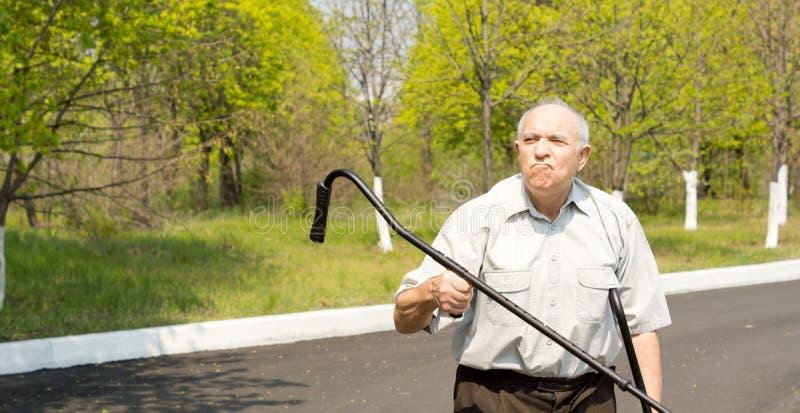 Homem idoso que acena sua muleta no ar imagens de stock