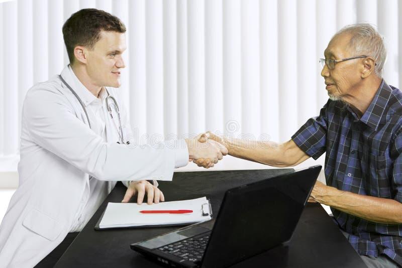 Homem idoso que agita as mãos com seu doutor fotografia de stock royalty free