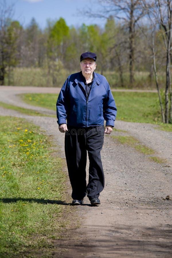 Homem idoso que anda na estrada imagens de stock