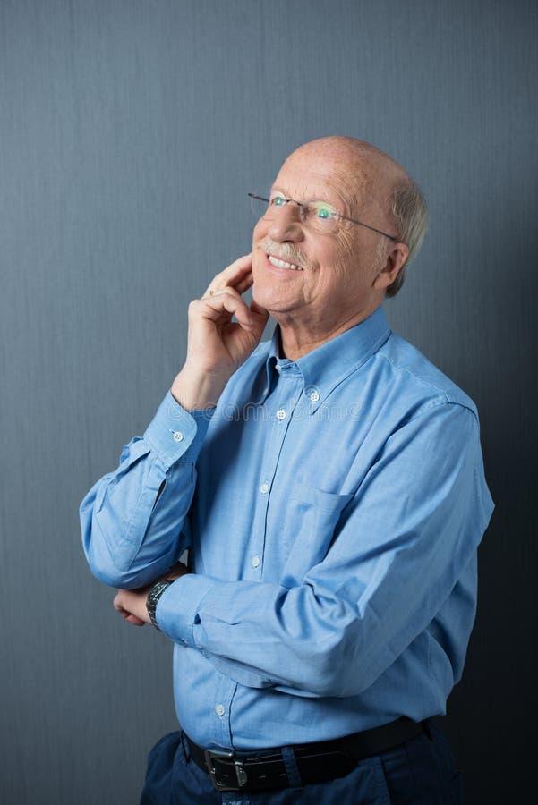 Homem idoso que está de pensamento com um sorriso feliz foto de stock royalty free