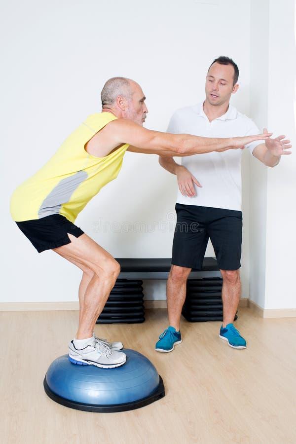 Homem idoso que exercita com instrutor pessoal fotos de stock