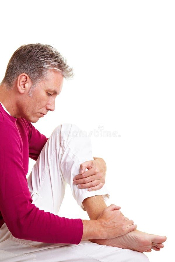 Homem idoso que faz massagens seus pés fotografia de stock royalty free