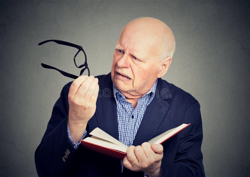Homem idoso que guarda o livro, vidros que têm os problemas da visão incapazes de ler fotos de stock