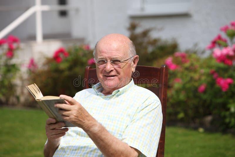 Homem idoso que lê um livro na luz do sol imagem de stock royalty free