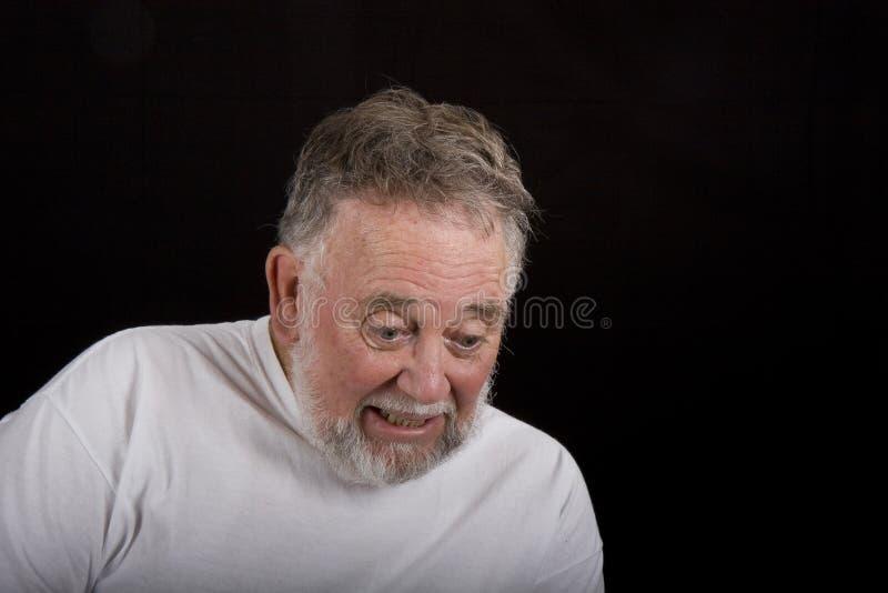 Homem idoso que olha abaixo do Scared fotos de stock royalty free