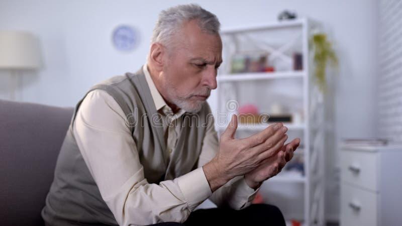 Homem idoso que olha as palmas, pensando sobre a vida, processo de envelhecimento, aposentadoria foto de stock royalty free