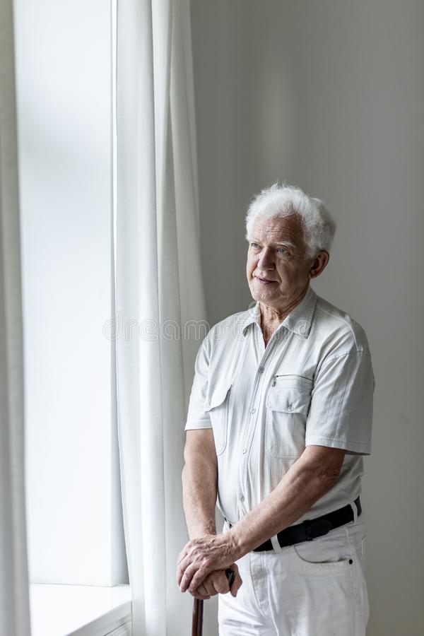 Homem idoso que sustenta um bastão e uma posição em uma sala ao lado de uma janela imagens de stock royalty free