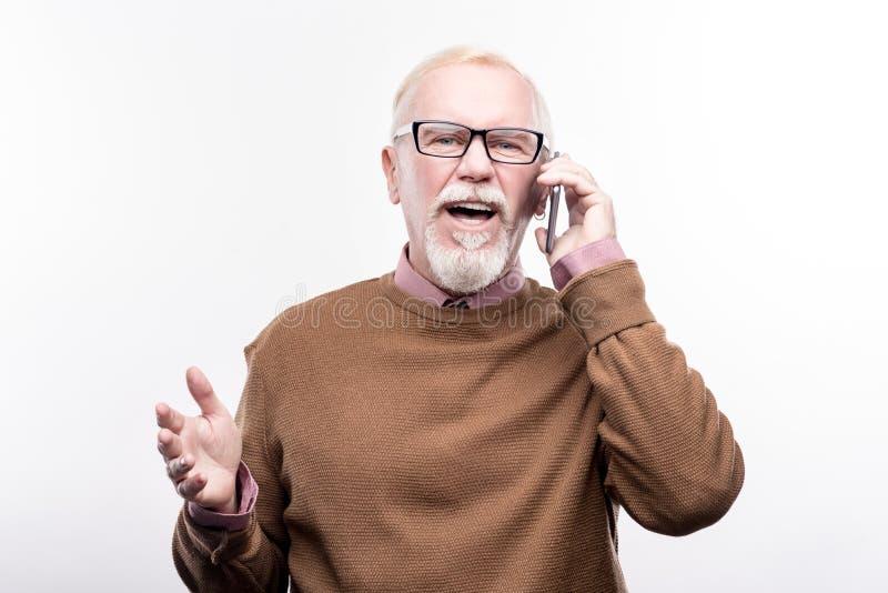 Homem idoso que tem a conversação emocional no telefone imagem de stock