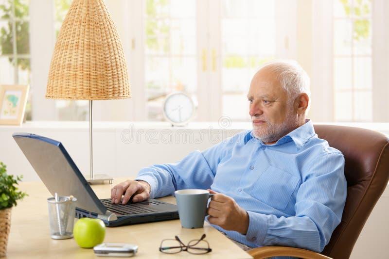 Homem idoso que usa o computador, comendo o café